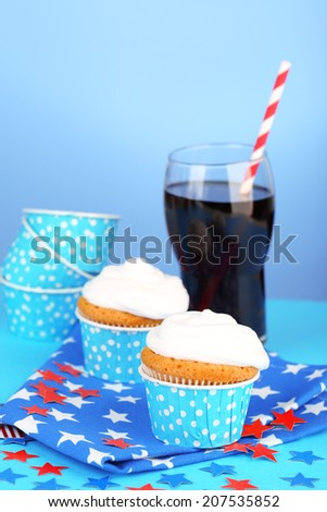 American patriotic holiday cupcakes and glass of cola on blue background - stock photo