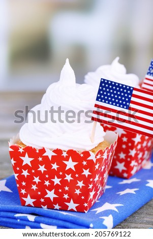 American patriotic holiday cupcakes on wooden table - stock photo