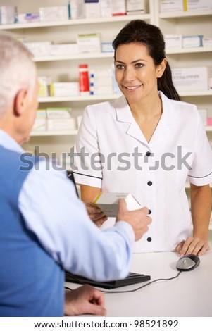 American pharmacist dispensing to senior man - stock photo