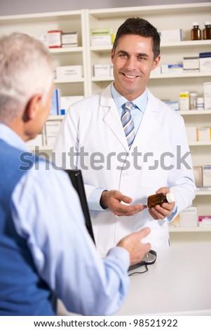 American pharmacist with senior man in pharmacy - stock photo