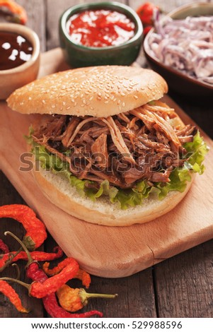 American pulled pork burger sandwich with lettuce and dipping sauces