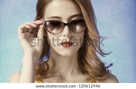 American redhead girl in sunglasses. Photo in old 60s style. - stock photo