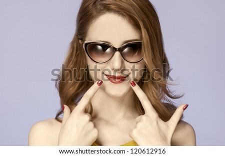 American redhead girl in sunglasses. Photo in 60s style. - stock photo