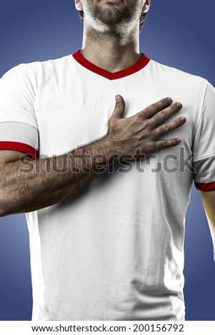 American soccer player, listening to the national anthem with his hand on his chest. On a blue background. - stock photo