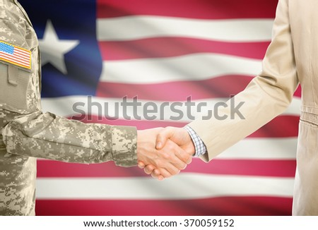 American soldier in uniform and civil man in suit shaking hands with national flag on background - Liberia