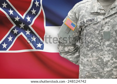 American soldier with US state flag on background - Mississippi - stock photo