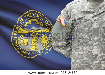 American soldier with US state flag on background - Nebraska - stock photo