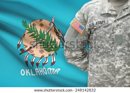 American soldier with US state flag on background - Oklahoma - stock photo