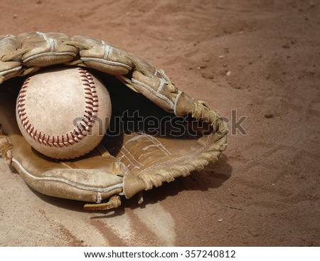American sport of baseball image of close up view with old, rough baseball and worn leather mitt, or glove. Equipment is laying in the clay on top of home base. Vintage filter applied. Copy space