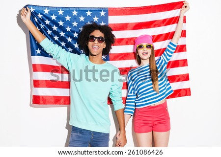 American style. Funky young couple smiling and looking at camera while standing against American flag - stock photo