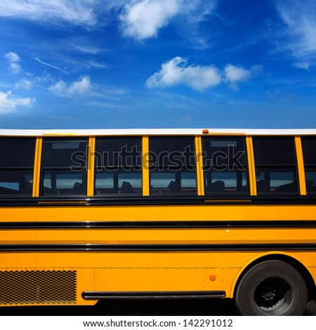 American typical school bus side view on blue sky day - stock photo