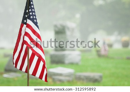 American veteran flag in a foggy cemetery. Vertical format. - stock photo