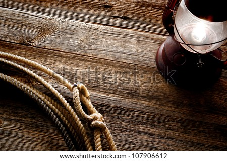 American West authentic rodeo cowboy lariat lasso noose with rawhide speed burner on weathered and aged barn wood background lit by an old vintage kerosene lantern lamp - stock photo