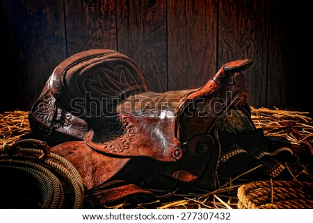American West legend authentic brown leather western saddle left behind by a rodeo cowboy in an old ranch wood barn - stock photo