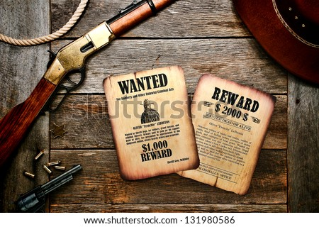 American west legend old west wanted sheriff poster and dead or alive search reward Marshall notice on antique wood desk with rifle shotgun and revolver with bullets ( documents created by author) - stock photo