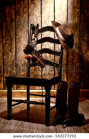 American West legend traditional brown cowboy hat and revolver gun in leather holster hanging on an old black wooden chair with authentic boots on wood floor in a vintage ranch western home - stock photo