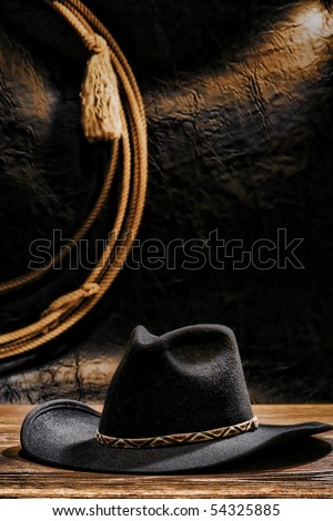 American West rodeo cowboy black felt hat and lasso hanging on a grunge wall