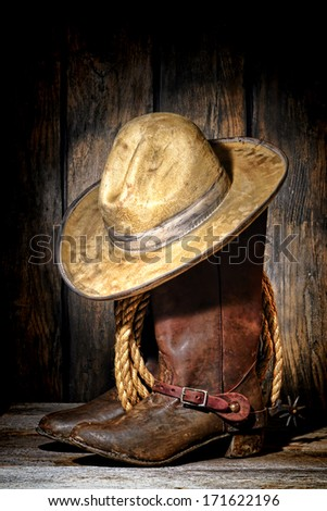 American West rodeo cowboy dirty and used white felt hat atop worn and muddy leather working rancher boots with vintage spurs and old ranching rope in an antique ranch barn - stock photo