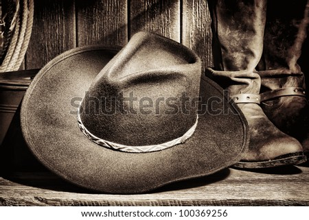 American West rodeo cowboy felt hat and authentic leather western riding boots with vintage ranching gear on weathered wood floor in an old ranch barn - stock photo