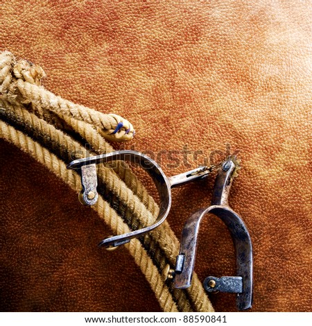 American West rodeo cowboy lariat lasso with cutting and roping spurs on old brown leather grunge background - stock photo