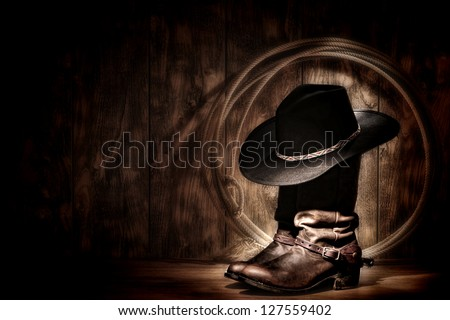 American West rodeo cowboy traditional black felt hat resting atop worn leather working rancher roper boots and lasso lariat in a vintage ranch wood barn lit in moonlight diffused glow - stock photo