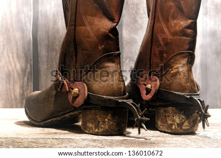 American West rodeo cowboy traditional leather boots distressed and worn rear heels with antique Western riding spurs in an old ranch wood barn with soft diffused haze - stock photo