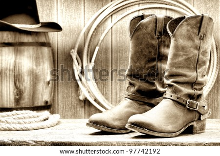 American West rodeo cowboy traditional leather working rancher roper boots with authentic Western riding spurs in front of vintage ranch wood barn with lariat lasso in nostalgic grunge sepia - stock photo