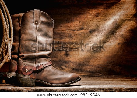 American West rodeo cowboy traditional leather working roper boots with authentic Western riding spurs and roping lasso lariat on a vintage ranch barn old weathered wood floor - stock photo