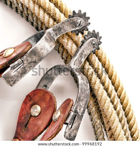 American West rodeo cowboy western riding spurs with worn rowel on authentic ranching lariat lasso over white - stock photo