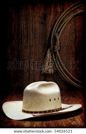 American West rodeo cowboy white hat and authentic Western lasso hanging on a wood wall in a ranching barn