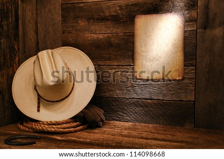 American West rodeo cowboy white straw hat and authentic western rope lasso on weathered wood floor in an old ranch barn with aged antique poster notice on wall