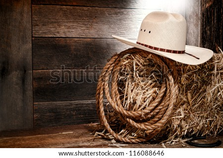 American West rodeo cowboy white straw hat with traditional western ranching rope on a bale of hay in an old wood ranch barn lit by diffused light - stock photo