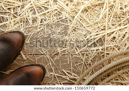 American West rodeo traditional roper leather cowboy boots and authentic lariat lasso loop on aged wood barn floor covered with hay straw in an old ranch barn - stock photo