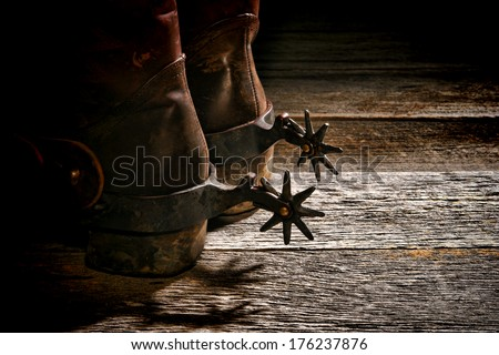 American West rodeo vintage Western riding spurs on traditional leather cowboy boots with dirty worn heels on old weathered wood planks in a western ranch - stock photo