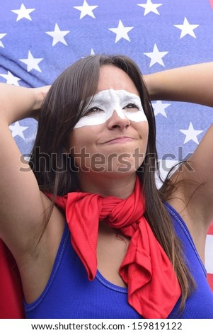 American woman Latin descent, disappointed with flag of United States of America in the background ground - stock photo