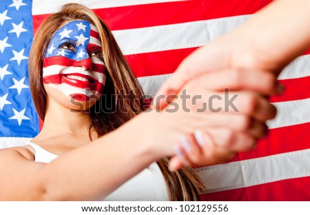 American woman with the USA flag painted on her face handshaking someone - stock photo