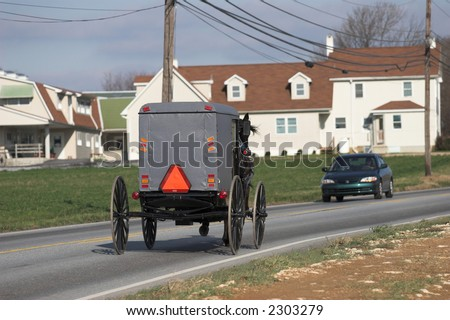 amish cart and car passing each other - stock photo