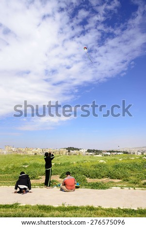 Amman, Jordan - April 03, 2015: View of three jordanian boys playing with kite in Amman Citadel. A kite is an aircraft consisting of one or more wings tethered to an anchor system used for recreation - stock photo