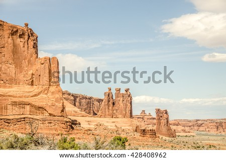 Among the named formations in Arches are the Three Gossips in the middle and Sheep Rock to their right - stock photo