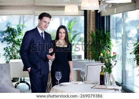 Amorous and a romantic dinner in a restaurant. Young couple visits a restaurant. woman holding a man's arm while the man and woman looking at the camera dressed in elegant clothes - stock photo