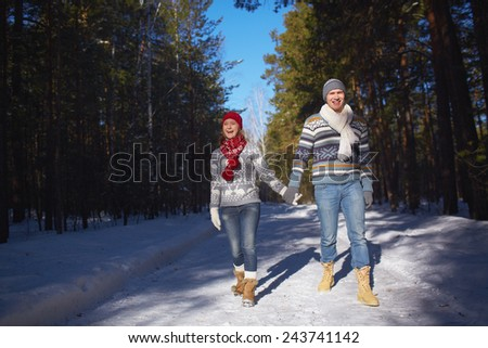 Amorous and ecstatic couple taking walk in winter forest - stock photo