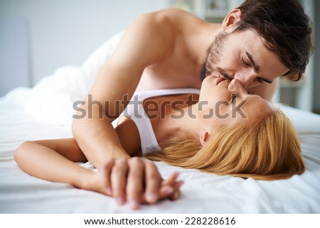 Amorous couple cuddling in bed - stock photo