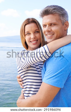 Amorous couple in embrace looking at camera by the sea - stock photo