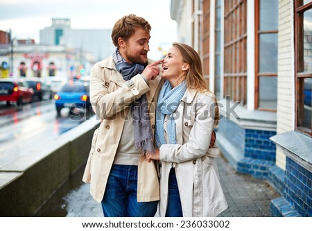 Amorous couple in trench coats having fun outside