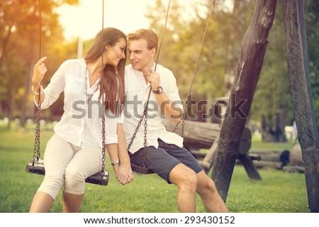 Amorous couple on romantic date on swings outdoor  - stock photo