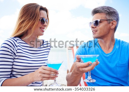 Amorous couple with cocktails spending vacation at summer resort
