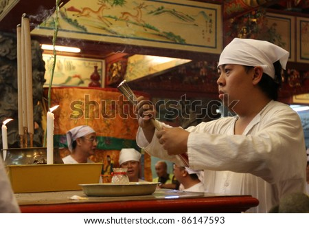 AMPANG, MALAYSIA – OCT 05: A Taoist devotee lights up the prayer joss-sticks at the Lam Thian Kiong Temple to start a prayer ceremony at the 'Nine Emperor Gods' Festival on October 05, 2011 in Ampang, Malaysia.