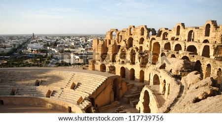 Amphitheatre with El Djem city skyline in Tunisia.  Arches and auditorium of roman biggest amphitheater in africa with city skyline of El Djam in the background, Tunisia - stock photo