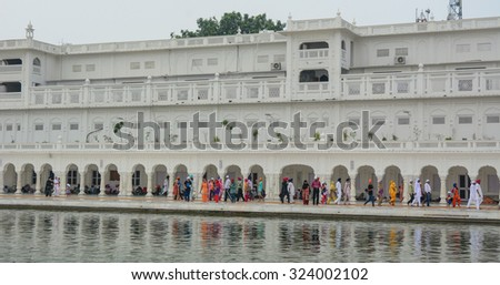 AMRITSAR, INDIA - JUL 18, 2015. Sikh pilgrims in the Golden Temple during celebration day in Amritsar, Punjab, India. Harmandir Sahib is the holiest pilgrim site for the Sikhs. - stock photo