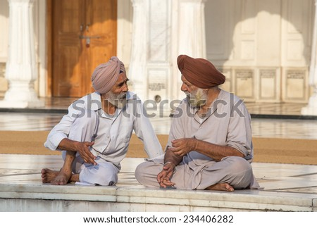 AMRITSAR, INDIA - SEPTEMBER 27, 2014: Unidentified Sikh men visiting the Golden Temple in Amritsar, Punjab, India. Sikh pilgrims travel from all over India to pray at this holy site. - stock photo